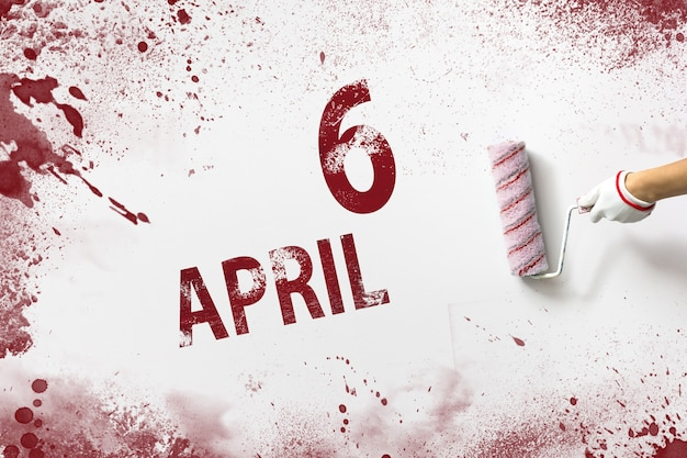 6 april. dag 6 van de maand, kalenderdatum. de hand houdt een roller met rode verf vast en schrijft een kalenderdatum op een witte achtergrond. lente maand, dag van het jaar concept.