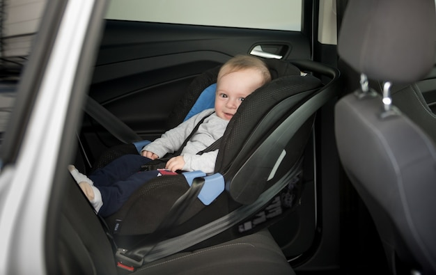 6 maanden oude babyjongen zit in kinderzitje in de auto