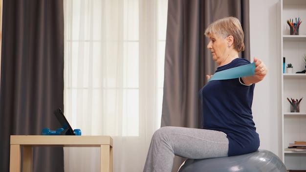 60 jaar oude vrouw die traint met behulp van een weerstandsband die naar online fitnessles kijkt. online training leertechnologie oude vrouw tillen training gezonde levensstijl sport fitness workout thuis met