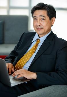 60s aziatische senior succesvolle executive business mannelijke ondernemer zittend, leunend achterover op de bank in het overdekte kantoor, laptop gebruiken voor technologie, werken met vertrouwen, glimlachend met positiviteit.