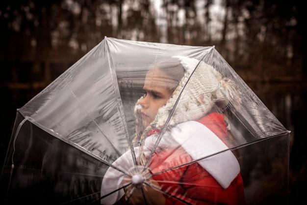 7-8 jaar meisje in een rode jas met transparante paraplu alleen wandelen in voorjaar bos