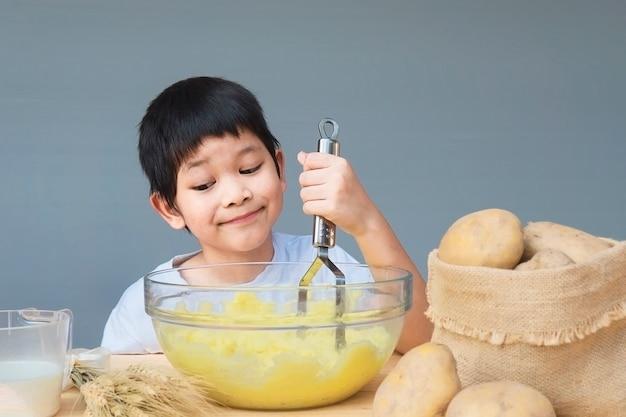 7 jaar jongen die fijngestampte aardappels gelukkig maakt