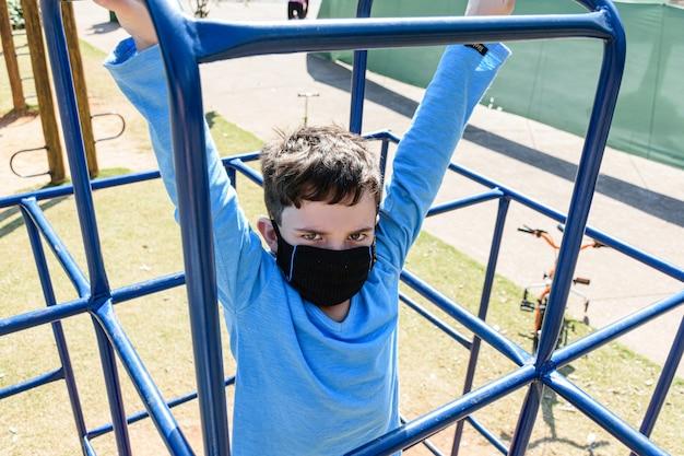 8-jarig kind dat met een boos gezicht staart, speelt op een klimspeelgoed van een park.