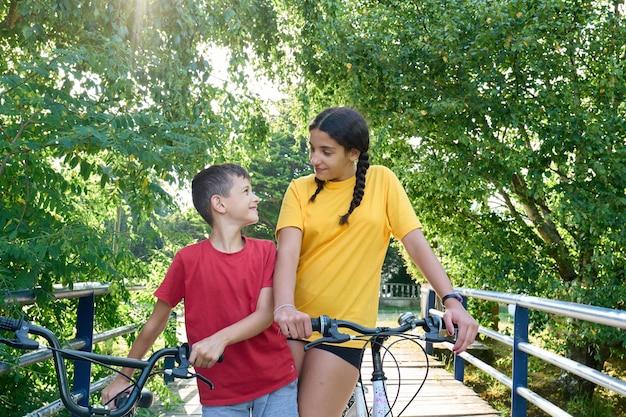 8-jarige jongen en een tienermeisje staan bij hun fietsen, broer en zus bond concept