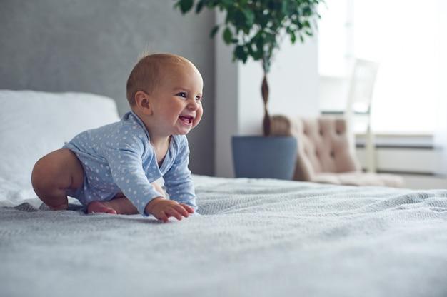 8 maanden oude gelukkige babyjongen die op bed thuis kruipt