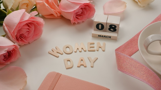 8 maart gelukkige vrouwendag op witte tabla-achtergrond versierd met roze bloemen en lint