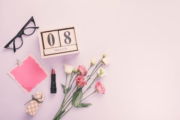 8 maart inscriptie met papier en roze bloemen op tafel