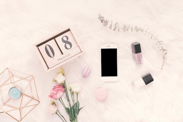 8 maart inscriptie met smartphone, bloemen en snoep op deken