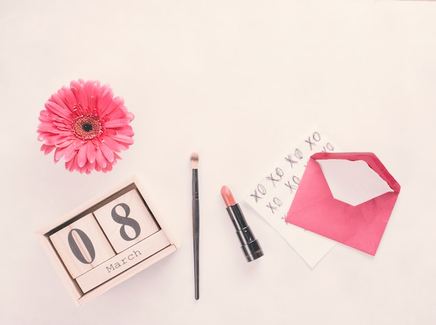 8 maart-inscriptie op houten blokken met bloem en lippenstift op tafel