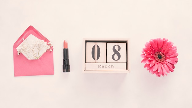 8 maart-inscriptie op houten blokken met bloem en lippenstift