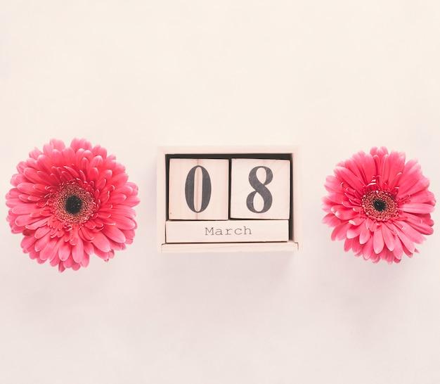 8 maart-inscriptie op houten blokken met bloemen op tafel