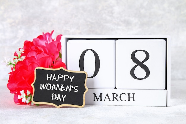 8 maart, internationale vrouwendag. houten eeuwigdurende kalender, roze bloemen en bord.