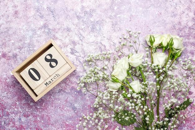 8 maart vrouwendagkaart met witte bloemen, snoepjes en een kopje thee