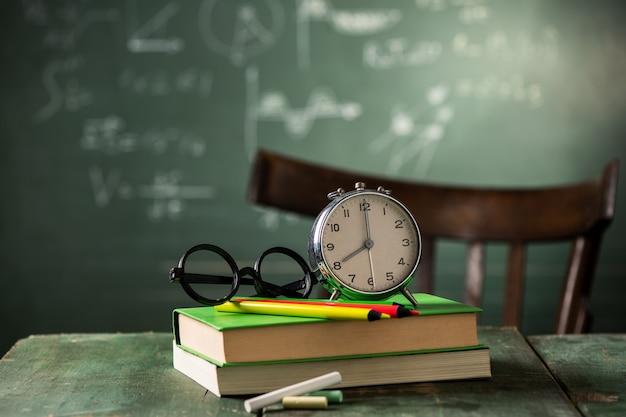 8 uur terug naar schoolconcept. wekker op boeken met bord op achtergrond