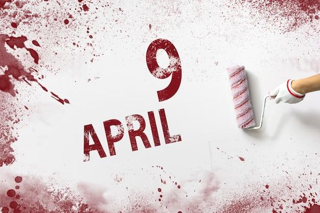 9 april. dag 9 van de maand, kalenderdatum. de hand houdt een roller met rode verf vast en schrijft een kalenderdatum op een witte achtergrond. lente maand, dag van het jaar concept.