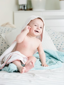 9 maanden oude babyjongen zittend op bed bedekt met handdoek na het baden