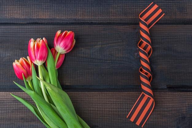 9 mei achtergrond - rode tulpen, george lint op de houten achtergrond. overwinningsdag of vaderland verdediger dag concept. bovenaanzicht, kopieer ruimte voor tekst