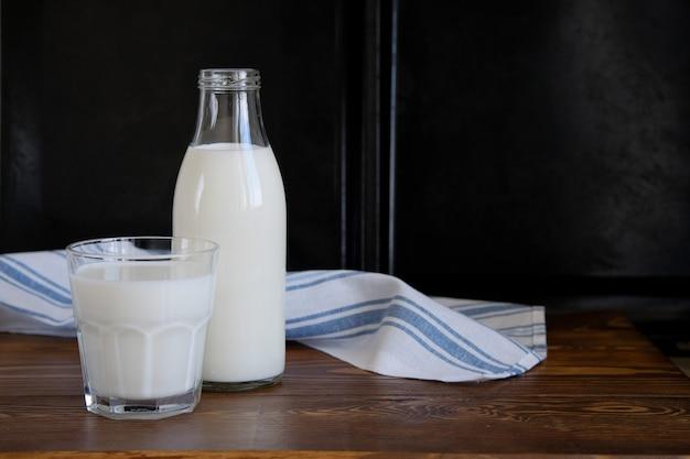 Свежее молоко в стеклянной бутылке и кружке на деревянном столе