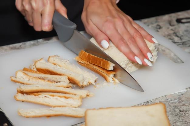 à â¡hef snijdt korsten van brood voor salade. proces van het bereiden van heerlijke salade