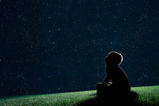 Ã'â kind zit 's nachts op het gras en kijk naar de nachtelijke hemel