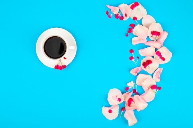 à â¡up van koffie en rozenblaadjes op een blauwe tafel. goedemorgen concept
