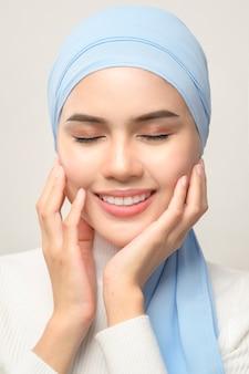 A close up van jonge mooie moslimvrouw met hijab geïsoleerd op een witte muur