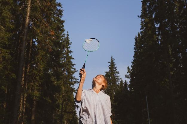 € ¢ jonge blanke vrouw speelt badminton op een achtergrond van blauwe lucht en bos.