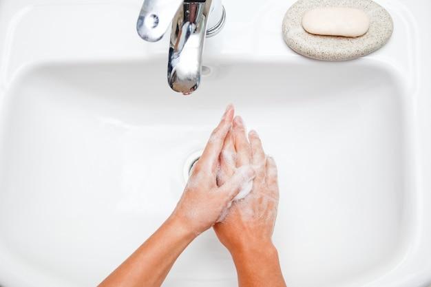 A handen wassen met zeep onder de kraan met water