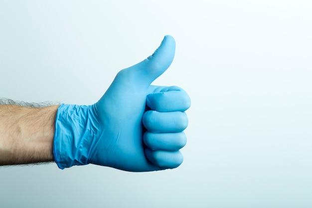 «likeâ» in een medische handschoen. doctor's hand in een blauwe medische handschoen op een lichte achtergrond.