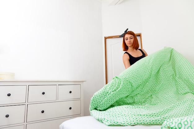 à verliezen van jonge vrouw in spijkerbroek, en zwart t-shirt doet huishoudelijke klusjes, verwijdert het bed met wit en groen geometrisch beddengoed in een slaapkamer met witte muren en een ladekast
