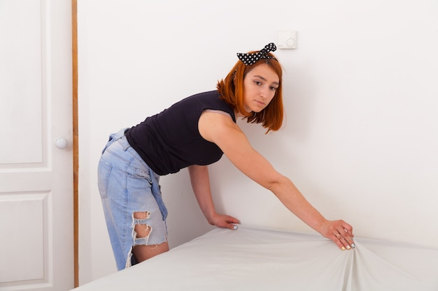 à verliezen van jonge vrouw in spijkerbroek, en zwart t-shirt reinigt het bed van wit-groen geometrisch beddengoed in een slaapkamer met witte muren en een ladekast