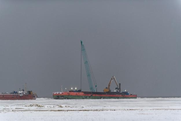 Aak met kraan. baggerschip aan het werk op zee. sterke mist in de arctische zee. bouw marine offshore werken.