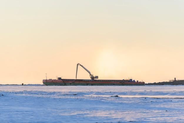 Aak met kraan. baggerschip aan het werk op zee. zonsondergang in de arctische zee. bouw marine offshore werken. dambouw, kraan, schuit, baggerschip.