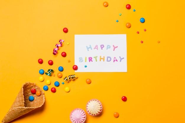 Aalaw; edelstenen en streamers van de kegel dichtbij het gelukkige verjaardagsbericht op gele achtergrond