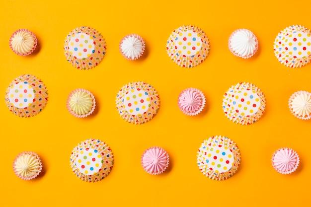 Aalaw met stippen papieren cakevormen in een rij op gele achtergrond