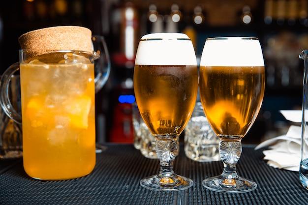 Aan de bar staat een transparante karaf met sinaasappelsap en ijsblokjes en twee glazen bier.