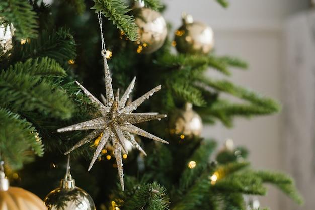 Aan de boom hangen kerststerren en ballen, versierd met lichtjes