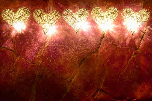 Aan de bovenkant van het frame zijn vijf handgemaakte gevlochten decoratieve harten, verlicht door lichten tegen een roodmarmeren achtergrond. onderaan is er een plaats voor inscripties voor verschillende feestdagen