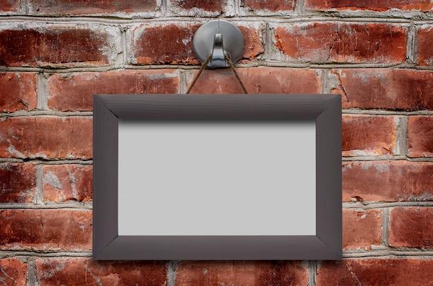 Aan de bruine bakstenen muur hangt een houten frame