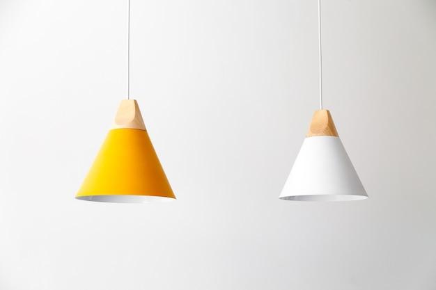 Aan de kabels hangen witte en gele lampen met lichte houten onderdelen