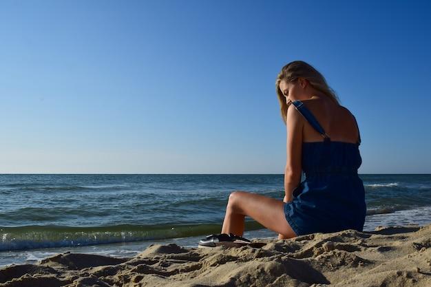 Aan de kust tegen de achtergrond van de lucht zit een blond meisje, naast haar op het zand liggen haar pantoffels