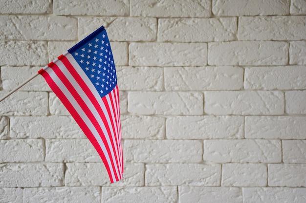 Aan de linkerkant van het frame staat de amerikaanse vlag op een bakstenen muurachtergrond aan de rechterkant is een lege