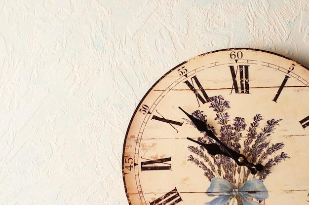 Aan de muur hangt een decoupage klok in provençaalse stijl. romeinse cijfers.