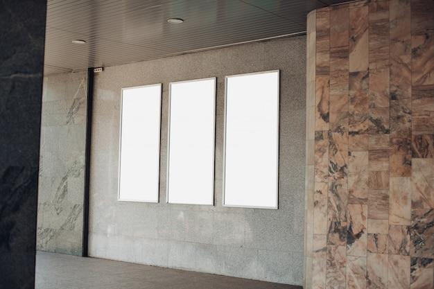 Aan de muur van het gebouw staan drie reclameborden