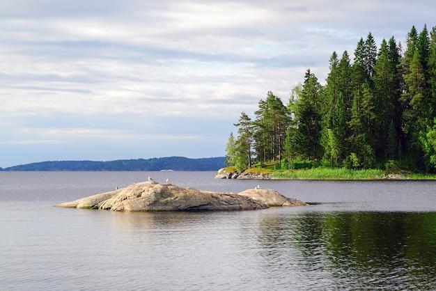 Aan de oever van het meer met een klein stenen eiland