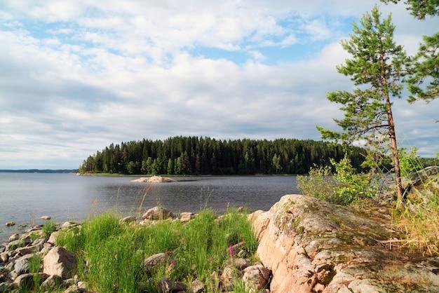 Aan de oever van het meer met eilanden in de verte