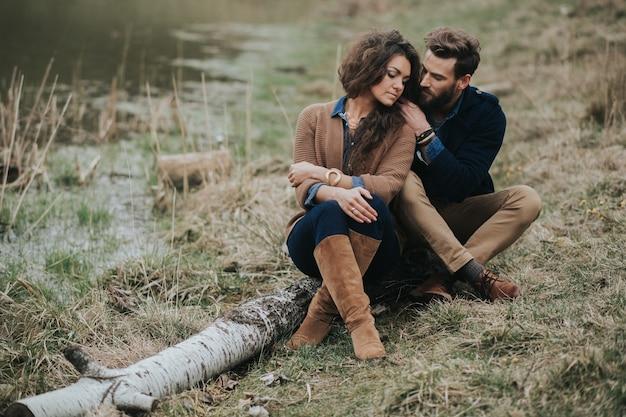 Aan de oever van het meer zitten gelukkige geliefden. jong koppel is knuffelen op herfstdag buitenshuis. een bebaarde man en een gekrulde vrouw verliefd.