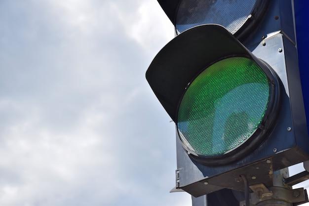 Aan de rechterkant van het frame is er een verkeerslicht met een gloeiend groen licht tegen de lucht. er is een plaats aan de linkerkant voor een inscriptie
