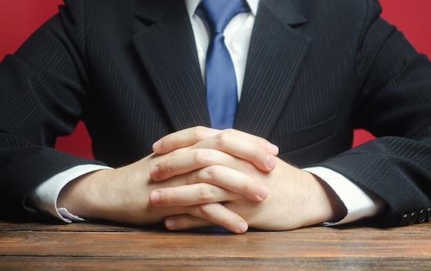 Aan de tafel zit een man met gevouwen armen. klaar om te luisteren naar nieuws en kritiek