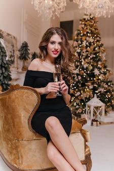 Aan de vooravond van kerstmis, schattige brunette met mooie lange benen, in zwarte jurk en met mooie manicure, champagne drinken uit kristalglas, zittend tegen nieuwjaarsversieringen